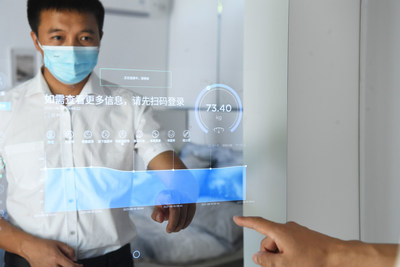 """Un hombre hace clic en el espejo para verificar su estado de salud en el Parque Inteligente Chongqing Lijia, donde las personas pueden experimentar """"un día de vida inteligente"""", como parte de las exposiciones de la Smart China Expo 2021. (PRNewsfoto/iChongqing)"""